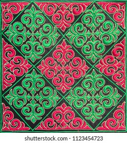 Beautiful embroidery in Kazakh style made of red & green squares on black velvet. Closeup. Selective focus
