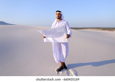 Beautiful Emirate Sheikh businessman studying project of future construction of complex, standing in middle of bottomless desert with white clean sand on clear warm day against blue sky. Swarthy