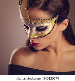 Beautiful emotion woman posing in fashion carnival mask with red lipstick and looking down. Closeup toned portrait. Art
