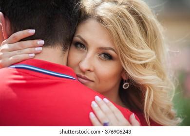 Beautiful emotional blonde bride hugging casual groom, closeup