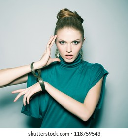 a beautiful emotional blonde in a green (blue) dress wearing wristbands over light blue background. studio shot