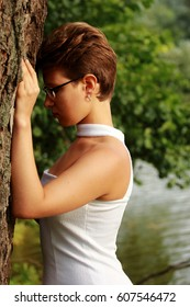 Beautiful emotional girl in a white dress standing at the tree. To the waist, wearing glasses, open shoulders.