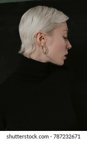 Beautiful emotional girl with white hair on a black background