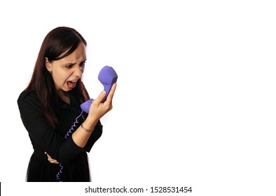 A beautiful emotional woman in a black dress is yelling in a handset on isolated white background. Copy space.