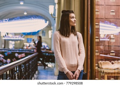 Beautiful emotional young woman looking in the window at the mall