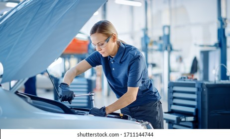 Beautiful Empowering Female Car Mechanic is Working on a Vehicle in a Service. She Looks Happy While Using a Ratchet. Specialist is Wearing Safety Glasses.