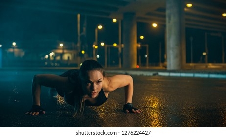 Beautiful Energetic Fitness Girl in Black Athletic Top and Shorts is Doing Push Up Exercises. She is Doing a Workout in an Evening Wet Urban Environment Under a Bridge.