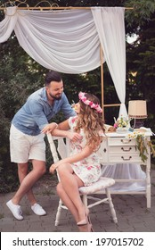 Beautiful engaged couple looking at each other, posing in a shabby chic vintage decor outdoor with a white chair and a white table with vintage objects on it