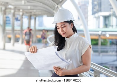 Beautiful Engineer Wear White Helmet for Security work. Hold a blueprint in hand  front of a Construction site .Construction and Engineering Concept.