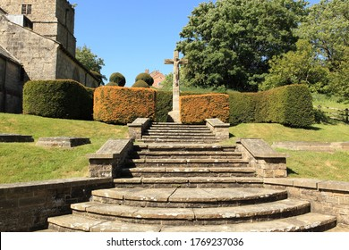 Beautiful English churchyard with curved stone steps leading to a statue of Jesus Christ on the cross