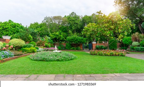Beautiful English cottage garden, colorful flowering plant on smooth green grass lawn and group of evergreen trees in good care maintenance landscaping of a public park under white sky and sunshine