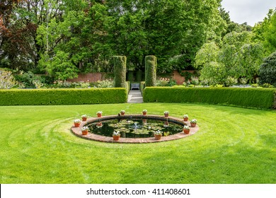 Beautiful English style garden with green lawn, trimmed rounded hedges, potted flower plants, water fountain & a bench in the distant background, all designed with European flair & tradition.