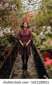 Beautiful Enigmatic Woman Standing in Glasshouse. Caucasian Girl with Short Brown Hair in Modest Dress Holding Flower Pot. Tenderness Elegant Female Model Eco Photoshoot in Indoor Garden