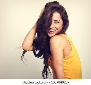 Beautiful enjoying fun laughing woman in yellow shirt with toothy smile holding the hand the long brown hair. Toned vintage portrait