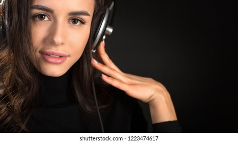 Beautiful enjoying young woman listening the music in wireless headphone with closed eyes on dark black background. Closeup