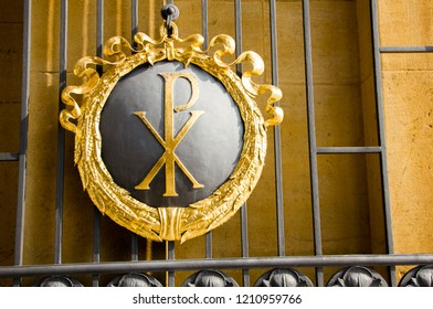 Beautiful entrance of a cemetery with Chi Roh symbol of a P and X, that is a form of christogram and represents the Christian belief.