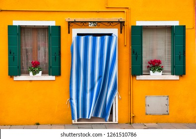 Beautiful entrance door with a striped white and blue curtain and two windows with flowers, seen from a street in Venice, Italy.