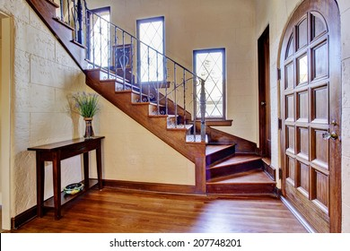 Beautiful entrance hallway in luxury house with wooden entrance door and staircase with iron railings