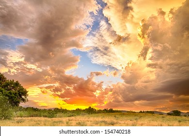 A beautiful epic sunset with blue sky behind the colorful majestic clouds. A scenic country landscape view looking west to the Colorado Rocky Mountains in Boulder County where the sky meets the land.