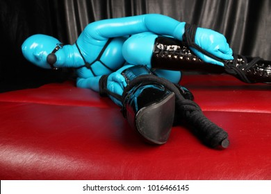 beautiful erotic sex doll woman posing in a blue zentai catsuit and has bondage with black ropes