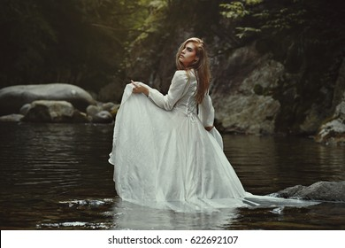 Beautiful ethereal woman in mystical waters. Fantasy pond