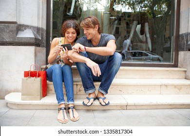 Beautiful ethnic diverse tourist couple on city holiday by clothing store with shopping bags using smartphone, smiling networking ourdoors. Technology people vacation, leisure recreation lifestyle.