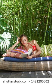 Beautiful ethnic diverse woman laying in tropical garden reading book on holiday hotel retreat, sunny light outdoors. Healthy female relaxing on lush vacation, healthy leisure recreation lifestyle.