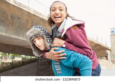 Beautiful ethnic diverse young students couple playful in skateboarding park, carrying girl on piggy back, fun smiling outdoors. Fashionable teenagers socialising games, leisure recreation lifestyle.