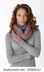 Beautiful ethnic woman in scarf and gloves over white background, looking at camera.
