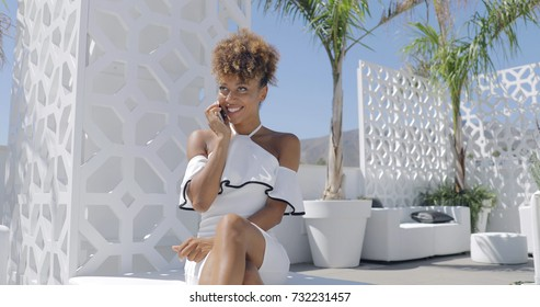 Beautiful ethnic woman wearing fashionable white dress and talking smartphone while sitting on luxurious hotel terrace in sunlight looking away cheerfully.