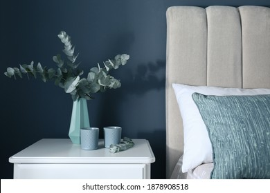 Beautiful eucalyptus branches and candles on nightstand in bedroom. Interior element