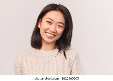 Beautiful euphoric teenage girl enjoying weekend at home looking and smiling at camera. Beautiful young woman Asian appearance with black hair and brown eyes stands isolated white background in Studio