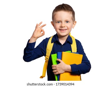 A beautiful European boy with blue eyes with books (notebooks) and a briefcase shows a hand sign. Schoolboy, student, first-grader.