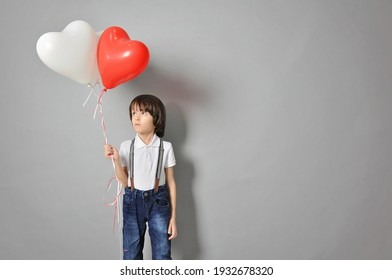 a beautiful European boy is thinking, holding heart-shaped balloons and looking at them. The concept of childhood and happiness