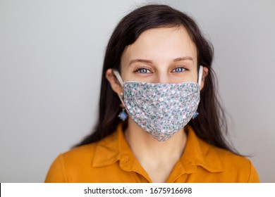 beautiful European girl with blue eyes in a handmade mask from the coronavirus. Design work protecting the security of disinfection of quarantine. Lack of masks . Pandemic houses white background