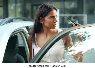Beautiful european girl stand between door and salon of her private automobile. Serious young brunette woman wear white dress, hold car key and looking somewhere. Concept of modern woman. City daytime