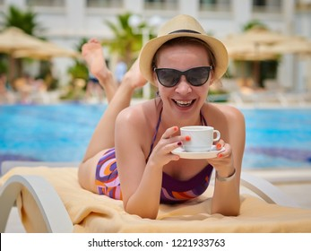 Beautiful European girl in a sunhat is laying on the sunbed at the hotel near the pool. She is having a rest, holding cup of coffee in her arms and smiling to the camera.