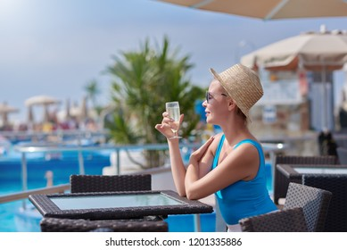 Beautiful European girl in the sunhat and sunglasses is sitting at the pool bar, she is enjoying her vacations, smiling and holding the glass of sparkling wine.