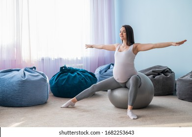 Beautiful european woman doing pregnant exercises. Expectant mother is doing exercises with a fitness sword. Yoga for expectant mothers.
