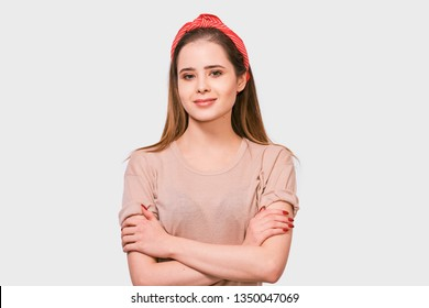 Beautiful European woman smiling, feels excitement, keeps hands crossed, posing against white background. Pretty female has joyful expression wearing red headband.