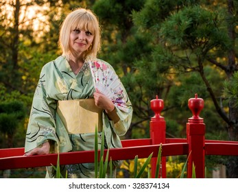 Beautiful european woman walking in the garden and wearing traditional japanese kimono and yellow umbrella