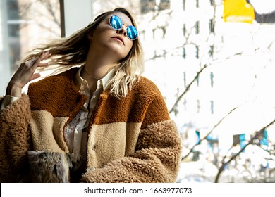 Beautiful European woman wearing brown fall fashion clothing is happily relaxing and enjoying a look outside the window in the city. the female model has brown blonde highlights and siting indoors
