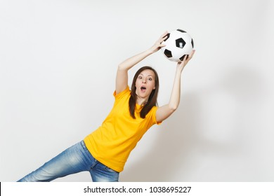 Beautiful European young goalkeeper woman, football fan or player in yellow uniform catching soccer ball in air isolated on white background. Sport, play football, health, healthy lifestyle concept