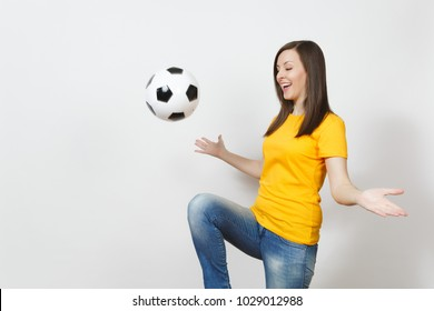Beautiful European young woman, football fan or player in yellow uniform juggling bouncing soccer ball on knee isolated on white background. Sport play football health, healthy lifestyle concept