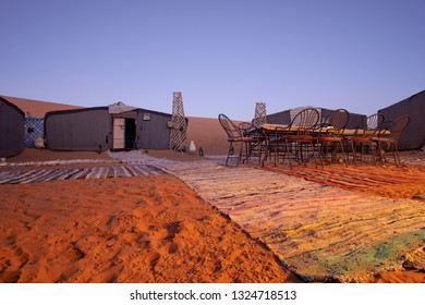Beautiful evening in a camp with carpets on the sand inside the Sahara desert in Morocco Africa