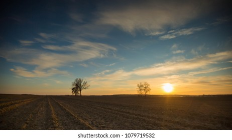 Beautiful evening colorful sky over plowed fields and trees, typical european village landscape.