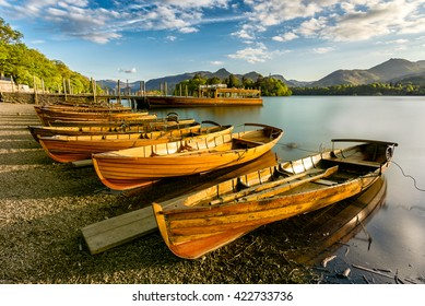 Beautiful evening golden light shining on row of rowing boats at Keswick Boat Launch in the English Lake District.