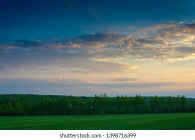 Beautiful evening landscape with bright clouds and green forest and field.