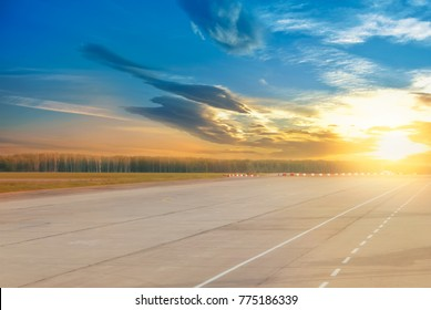Beautiful evening landscape of runway, airstrip in the airport terminal ready for airplane landing or taking off with dramatic cloudy sunset background. Travel aviation future concept at golden hour.
