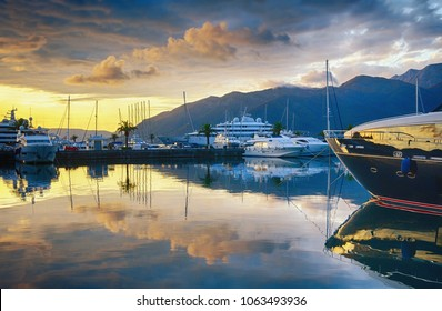 Beautiful evening landscape with yachts, golden clouds and reflections in the water. Montenegro, Tivat city, marina Porto Montenegro